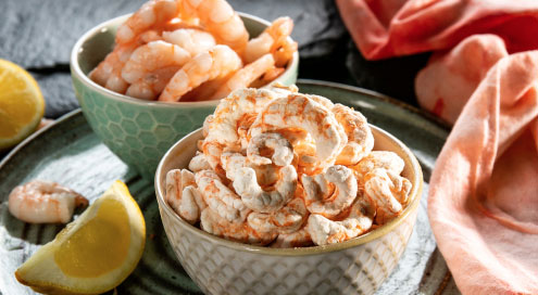 Freeze dried shrimp in shown in a bowl with slices of lemon