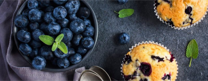 Bowl of blueberries with blueberry muffins