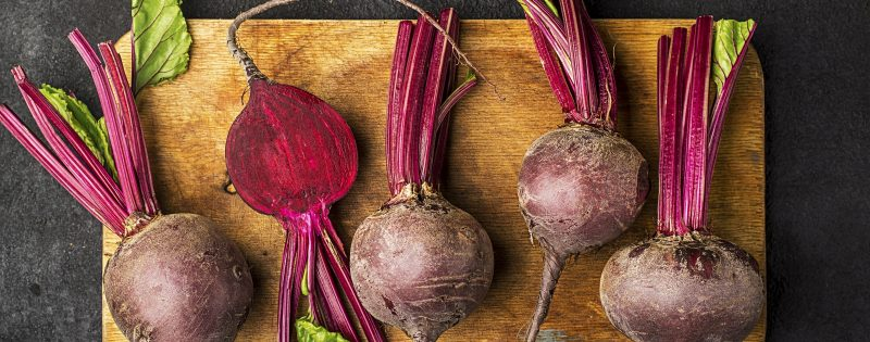 Raw organic farm beetroot on a vintage wooden cutting board on a plain black background. Top View